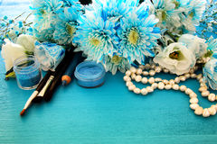 Delicate blue flowers arrangement next to pearls necklace and makeup Royalty Free Stock Image