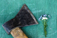 Delicate bouquet of flowers lying next to a rusty ax. Impersonation of the relationship between men and women Stock Image