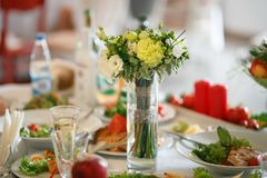 Bouquet of flowers on the served wedding table stock photos