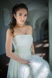 Delicate bride with curly hair standing near the Stock Image