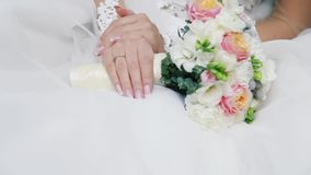 Delicate bride is holding marvelous bouquet. Golden ring. Wedding celebration. Traditions. Accessories of bride, pink. Roses, sweet bay, magnolia. No people stock video footage