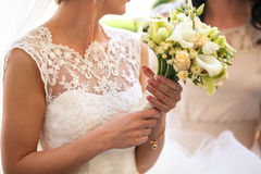Delicate bride holds a wedding bouquet of callas and roses Stock Photos