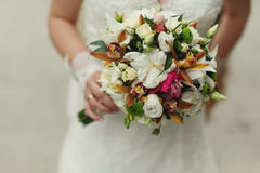Delicate bride's hands hold a wedding bouquet of roses and green Royalty Free Stock Photography