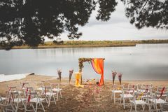 Delicate bright wedding arch of flowers and fabric on the sandy shore of a river or lake. Beautiful autumn decor, wedding royalty free stock photo