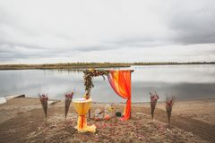 Delicate bright wedding arch of flowers and fabric on the sandy shore of a river or lake. Beautiful autumn decor, wedding royalty free stock photography