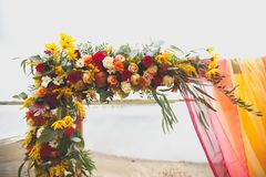 Delicate bright wedding arch of flowers and fabric on the sandy shore of a river or lake. Beautiful autumn decor, wedding stock image