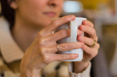 Delicate caucasian woman hands holding a white mug. Royalty Free Stock Images