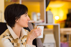 Delicate caucasian woman with short brown hair holding a white mug. Royalty Free Stock Image