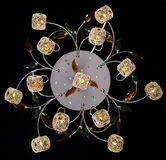 Delicate chandelier of color flower lamps isolated on black Stock Photography