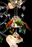 Delicate chandelier of color flower lamps isolated on black Stock Image