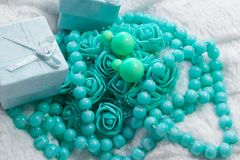 Delicate composition of costume jewelry color of mint and turquoise. Gentle color composition of mint and turquoise jewelry. Beads and roses from the box as a Royalty Free Stock Image
