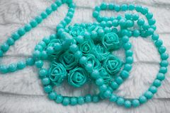 Delicate composition of costume jewelry color of mint and turquoise. Gentle color composition of mint and turquoise jewelry. Beads and roses from the box as a Stock Photos