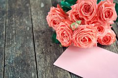 Delicate coral shade pink roses and gift with heart and letterhead on rustic wooden background. Valentine background. Holiday card royalty free stock photos