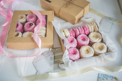 Delicate cream and pink marshmallows, packed in boxes of kraft paper royalty free stock photo
