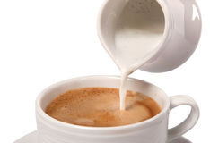 Delicate cream poured into cup of coffee Royalty Free Stock Images