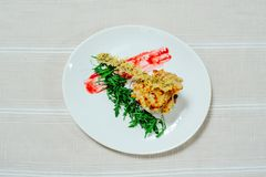 Delicate exquisite salad with migdal arugula turkey sun-dried tomatoes and greens in a white plate on a white tablecloth.  Stock Photos