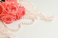 Delicate feminine theme. Pink coral roses trend color on a pale pink bra and pearl necklace on a white background. top view. close. Up. Stylish lingerie flat stock photo