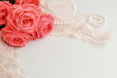Delicate feminine theme. Pink coral roses trend color on a pale pink bra and pearl necklace on a white background. top view. close. Up. Stylish lingerie flat royalty free stock photo