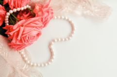 Delicate feminine theme. Pink coral roses trend color on a pale pink bra and pearl necklace on a white background. top view. close. Up. Stylish lingerie flat royalty free stock photos