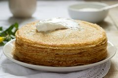 Delicate fishnet pancakes with sour cream. royalty free stock images