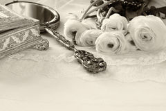 Delicate lace fabric, hand mirror and white flowers Stock Image