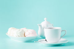 Delicate meringues, marshmallows and cup of english tea on white Stock Photo