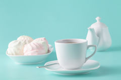 Delicate meringues, marshmallows and cup of english tea on white Stock Photography