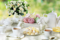 Delicate multicolored sweets. Delicate multicolored marshmallows and meringues on white openwork plate with tea set Stock Photo