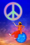Peace Symbol. A priest, a genie or an angel sitting on a planet, is holding the peace symbol in balance. Sky background Royalty Free Stock Photo