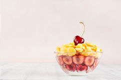 Delicate pink breakfast with golden corn flakes decorated cherry on white wood board. Decorative border with copy space. Stock Image
