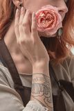The red-haired girl with a tattoo is holding a pink rose in her mouth. Layout for postcard. Delicate pink rose in the mouth of a red-haired young girl with a stock image