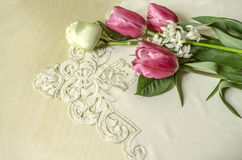 Delicate pink tulips with white rose and hyacinth. Lay on the embroidered tablecloth Stock Photo