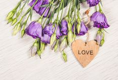 Delicate purple flowers and a wooden heart. Romantic concept. Delicate purple flowers and a wooden heart Royalty Free Stock Photo