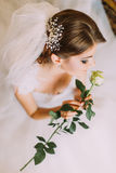 Delicate rose in the hands of fascinating young girl dressed white wedding gown.  Royalty Free Stock Images
