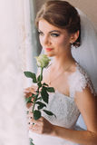 Delicate rose in the hands of young smiling bride dressed white gown Royalty Free Stock Image