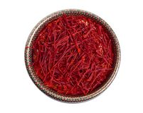 Delicate saffron threads, plucked from crocus flowers and dried. In the ethnic box. Isolated on white background.  stock photography