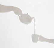 Delicate shadows of teapot pouring liquid into a cup held by fem Stock Photography