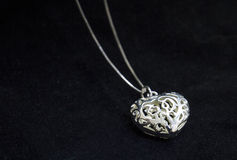Delicate silver heart on black backgound Stock Photo