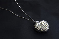 Delicate silver heart necklace on black Royalty Free Stock Image