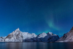 Delicate, soft northern lights over snowy mountains in moonlight royalty free stock image