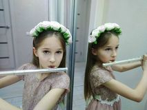 Delicate sound of flute. How to learn young talent to become the real musician? One of exercises - a game in front of the mirror. And if it is beautiful to dress stock image