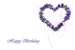 Delicate spring violets in the shape of a heart on a white background. Happy birthday Stock Image