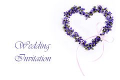 Delicate spring violets in the shape of a heart on a white background. Wedding invitation card. Beautiful fragile spring violets in the shape of a heart on a Royalty Free Stock Image