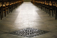 Delicate steel ventilation grille. In the old parquet floor in the cathedral Stock Photo