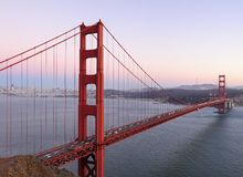 Delicate sunset hues behind Golden Gate Bridge. Delicate lilac, ping and purple hues play in the sky behind high-resolution stitched image of Golden Gate Bridge Stock Photos