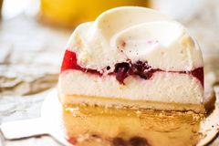 Delicate vanilla and raspberry sauce cake. Delicate vanilla and raspberries cake on a golden background- cut in half to expose the layers Royalty Free Stock Photos