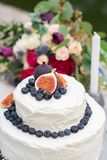 Rustic wedding white cake decorated with figs, blueberries royalty free stock photos