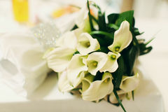 Delicate wedding bouquet made of callas lies on the white table Royalty Free Stock Photos