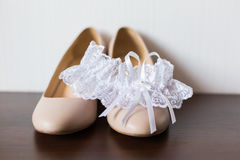 Delicate wedding garter and wedding shoes Stock Photo