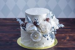 Delicate white bunk wedding cake decorated with an original design using mastic roses. Concept of festive desserts. Delicate white bunk wedding cake decorated royalty free stock photography